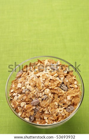 Glass bowl with muesli on green cloth with copy space. - stock photo