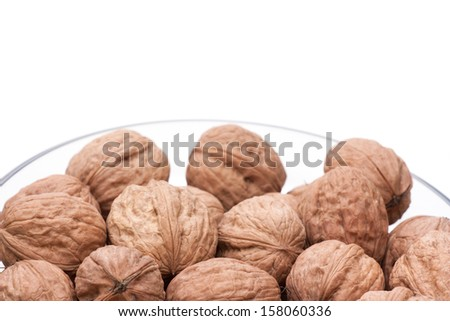 glass bowl with walnuts on a white background - stock photo