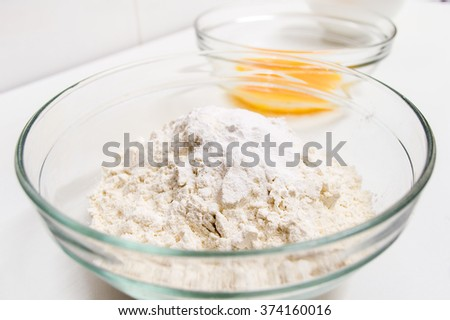 Glass bowl with wheat flour with another ingredients ready to prepare a cake at the kitchen