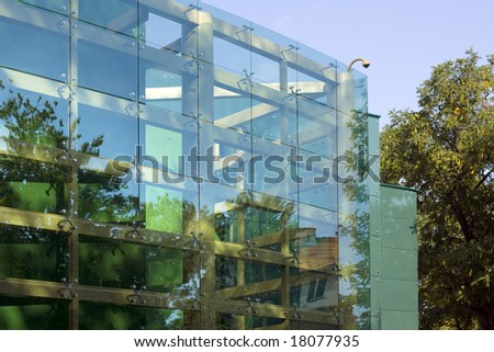glass building reflecting several trees and a blue sky - stock photo