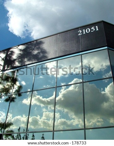 Glass building with clouds reflecting in windows - stock photo