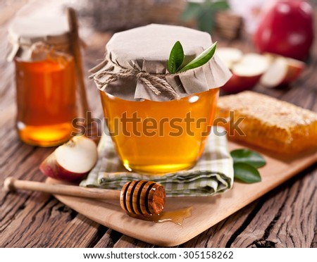 Glass cans full of honey, apples honeycombs on old wooden table. - stock photo