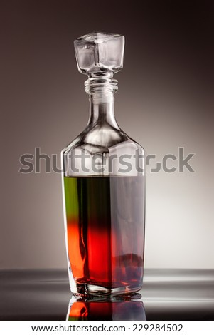 Glass carafe filled with multicolored liquid - stock photo