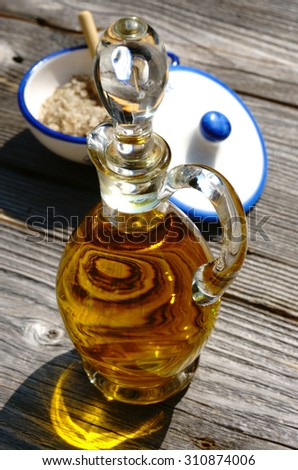 Glass carafe with olive oil and a porcelain bowl with fleur de sel salt on rustic wooden table - stock photo
