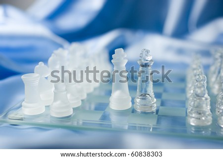 Glass chess figures on a chessboard with kings meeting on the battlefield to make an agreement. - stock photo
