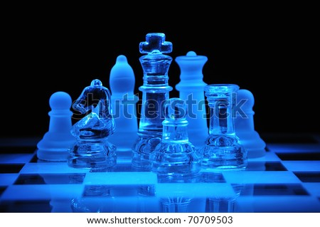 Glass chess figures on the chess field in a dark