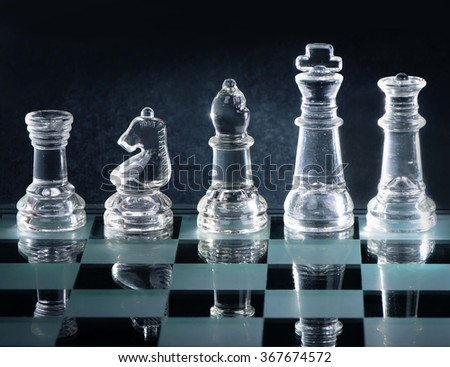 Glass chess is placed on black background