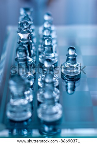 glass chess pawn in front with shallow depth of field blue toned - stock photo