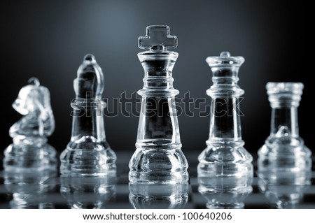 glass chess pieces is standing on board in dark - stock photo