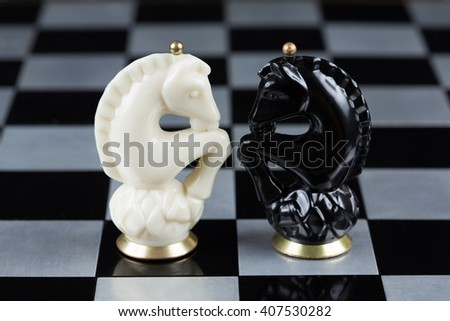 Glass chess pieces on a metal chessboard - stock photo