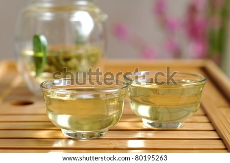 Glass Chinese tea set on wooden board with green tea leaves - stock photo