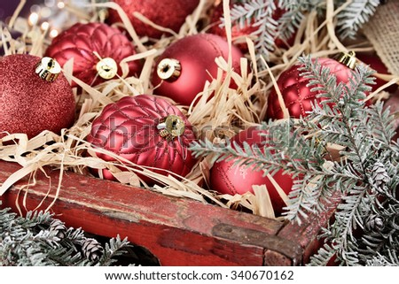 Glass Christmas ornaments packed in an old antique wooden box with snow covered pine boughs surrounding them. Extreme shallow depth of field with selective focus on center bauble.