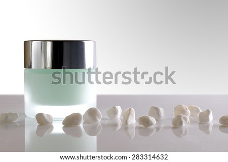 Glass closed jar with facial or body cream on white table with small white stones. Front view. White isolated background. - stock photo