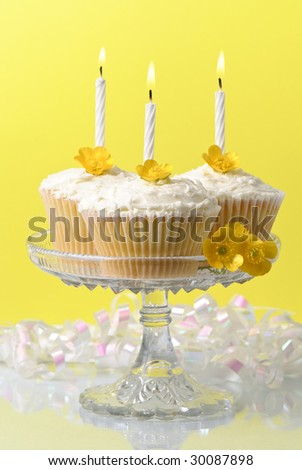 Glass comport of buttercup fairy sponge cakes with lit candles - stock photo