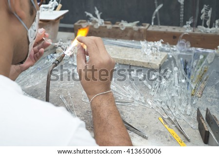 Glass craftsman making a glass sculpture.  - stock photo