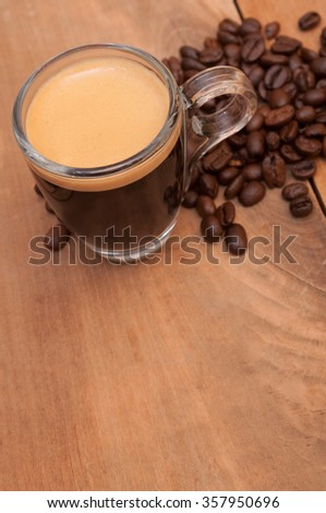 Glass Cup of Espresso Coffee on Wooden Table With Beans - Shallow Depth of Field