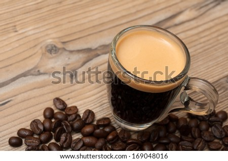Glass Cup of Espresso Coffee on Wooden Table With Coffee Beans - Shallow Depth of Field - stock photo