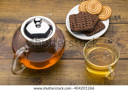 Glass cup of green tea and teapot with various cookies on white plate - stock photo