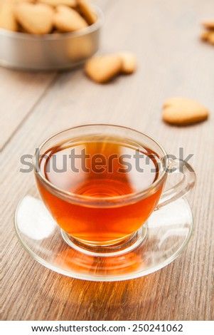 Glass cup of tea on a wooden table with a box of cookies. - stock photo