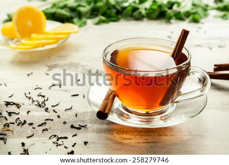 Glass cup of tea on a wooden table with sliced lemon and cinnamon. - stock photo