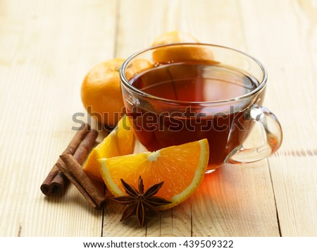 glass cup of  tea with anise, cinnamon and citrus fruits on the table  - stock photo