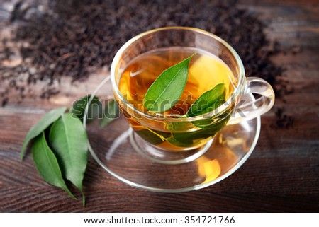 Glass cup of tea with green leaves on wooden background decorated with scattered tea - stock photo
