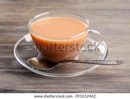 Glass cup of tea with milk on wooden background - stock photo