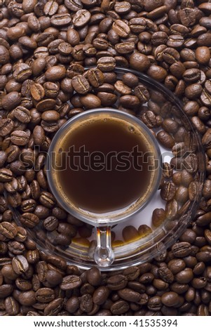 Glass cup of turkish coffee with coffee beans around from above - stock photo