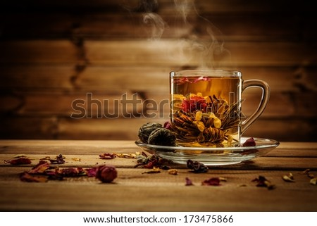 Glass cup with tea flower against wooden background  - stock photo