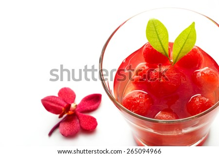 Glass delicious refreshing drink of vibrant watermelon with red orchid on white background, infusioned water - stock photo