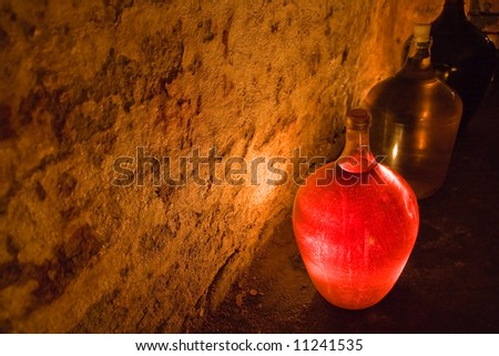 glass demijohn of rose wine lighten up by candle - stock photo