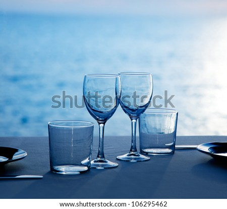 Glass dish cups and glasses on blue sea background - stock photo