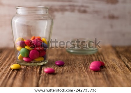 Glass dose with chocolate smarties is placed on old worn wooden board with cap in background and with few smarties spilled around - stock photo