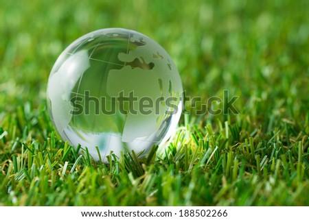 Glass earth globe in green grass field - stock photo