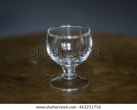 Glass empty shot glass for cocktail - the Small Shot. Isolated on a wooden background.