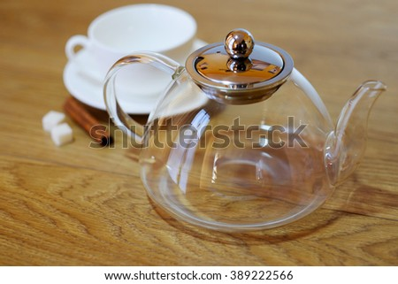 Glass empty teapot for tea, classic white cup with saucer, sugar and cinnamon on a wooden table background.  - stock photo