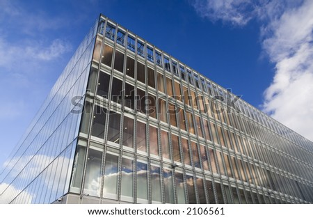 Glass faced office building against autumn sky - stock photo