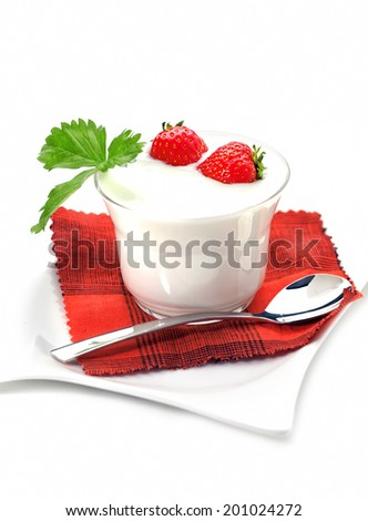 Glass filled with yogurt and decorated with strawberries, spoon and plate on white background