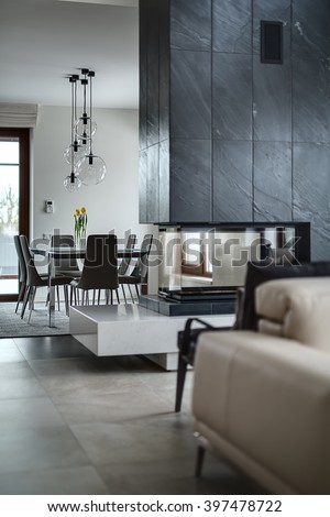 Glass fireplace with a black chimney. On the background there is a table with flowers in vases, chairs and glass round lamps over them, a brown glass door. Walls are light. On the floor there are - stock photo