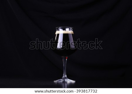 Glass full of dark beer over a black fabric background