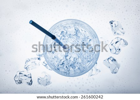 glass full of fresh water with ice cubes and thin cane, on blue background - stock photo