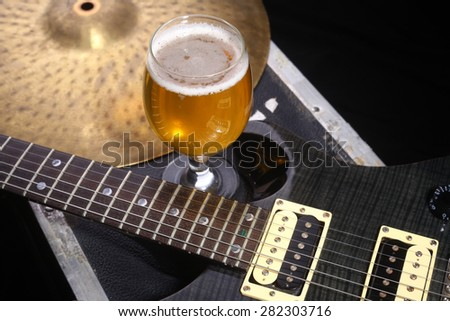 Glass full of light beer standing on a case with some music equipment - stock photo