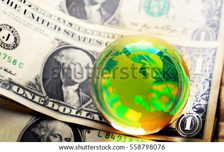 Glass globe and reflection of dollar bill
