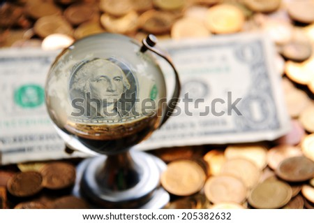 Glass globe and reflection of   dollar bill and  pile of coins - stock photo