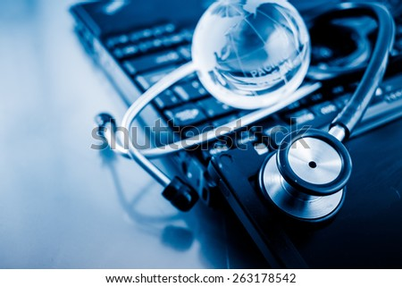 Glass globe and stethoscope on a computer keyboard.blue toned images. - stock photo