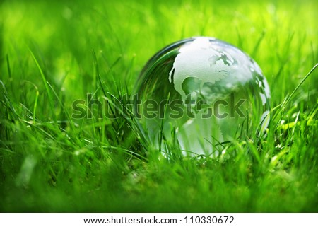 Glass globe in the grass concept for environment and conservation - stock photo