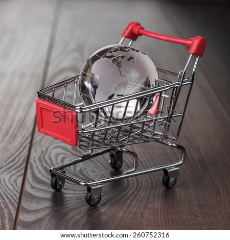 glass globe in the shopping trolley global market concept - stock photo