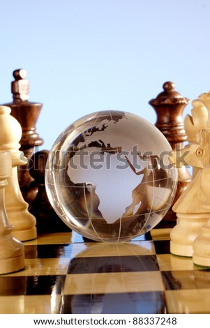 Glass globe on chess board - stock photo