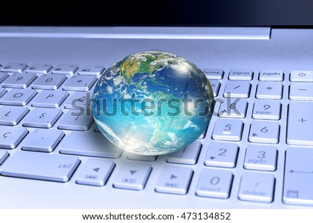 "Glass globe on laptop keyboard ""Elements of this image furnished by NASA """