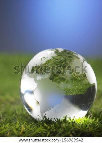 glass globe resting on the grass - stock photo